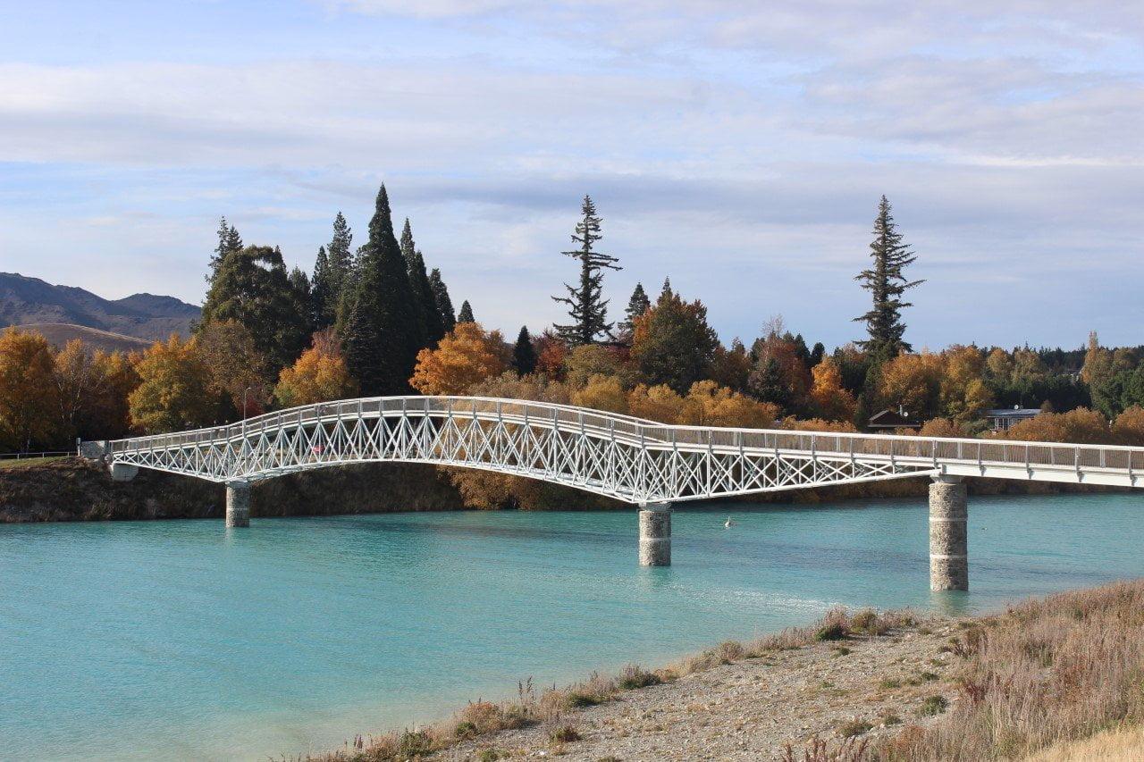 Nieuw-Zeeland fel blauwe water, de herfstkleuren en bergen op de achtergrond.