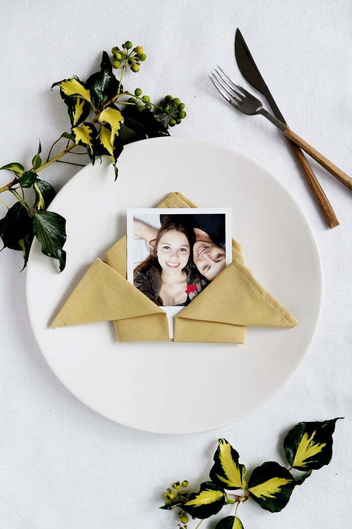 een servet gevouwen op een leuke en simpele manier je kunt er een naamkaart bij leggen, een foto, een gedicht of gewoon een bloemetje of een takje.